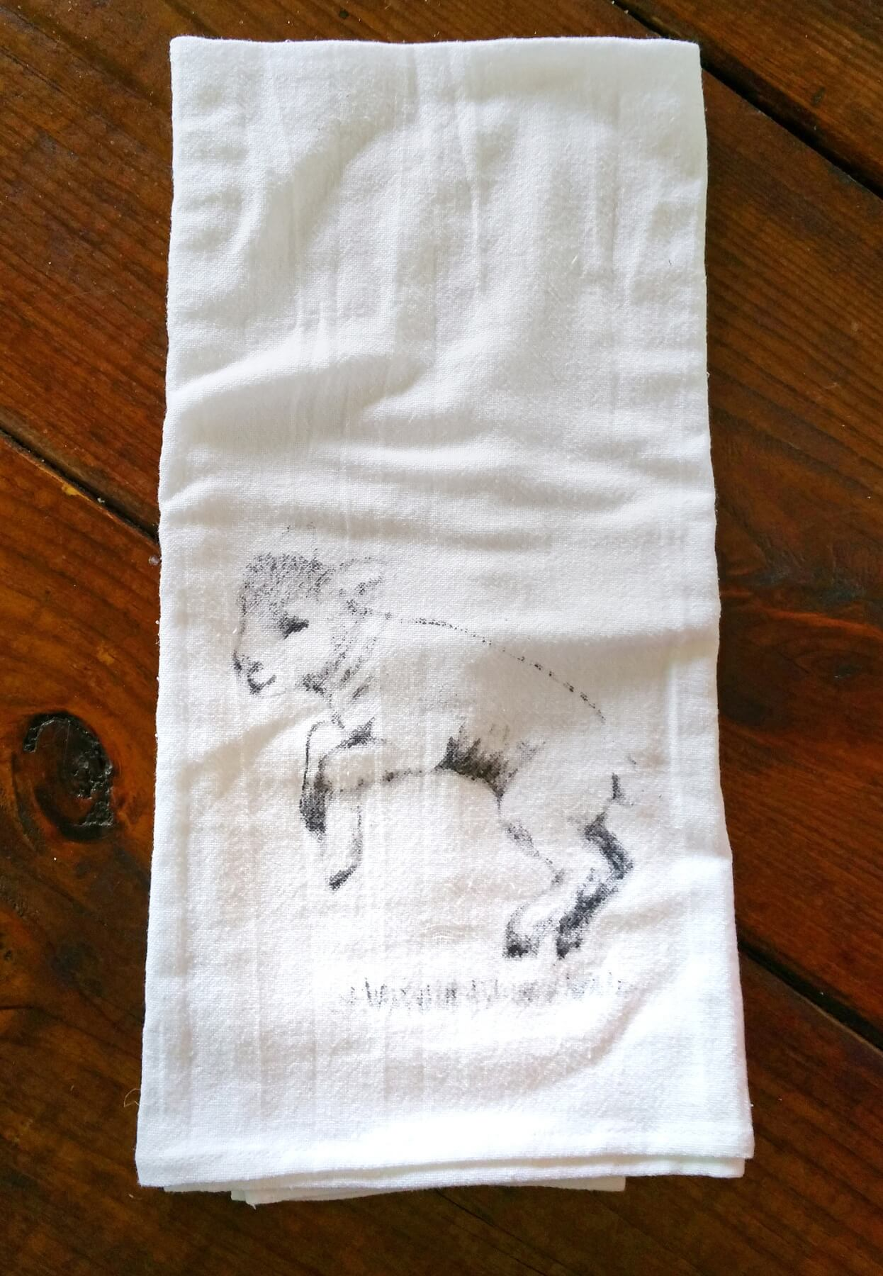 A sweet lamb hops around on this tea towel.