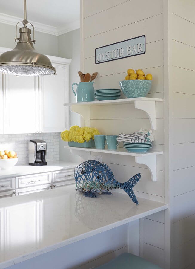 Kristin talked the builder into making some changes to the halfway-built beach house for a more custom look, including wood-planked walls and the marine pendants over the peninsula in the kitchen.