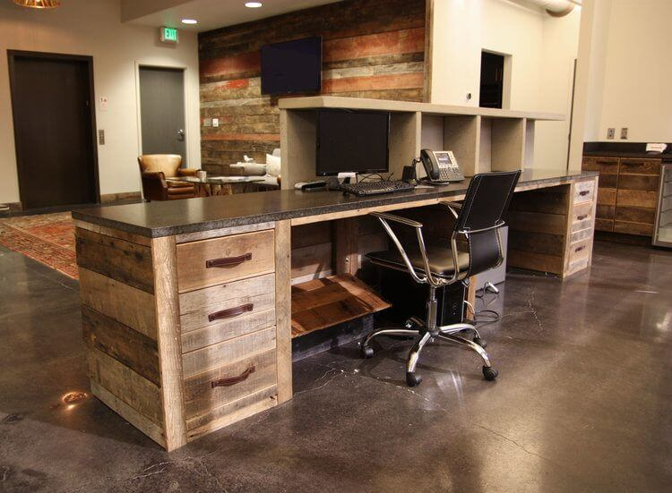 The reclaimed wood theme is woven throughout the space Here the receptionists reclaimed wood desk features some handsome leather handle pulls