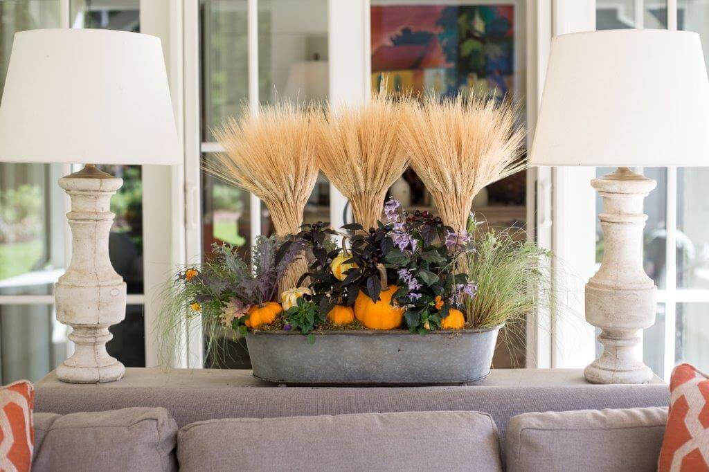 Cindy McCord of Cindy McCord Interior Design thinks outside the box when putting together a Halloween arrangement, like this fun and whimsical piece with stalks of wheat and deep greens and purples.