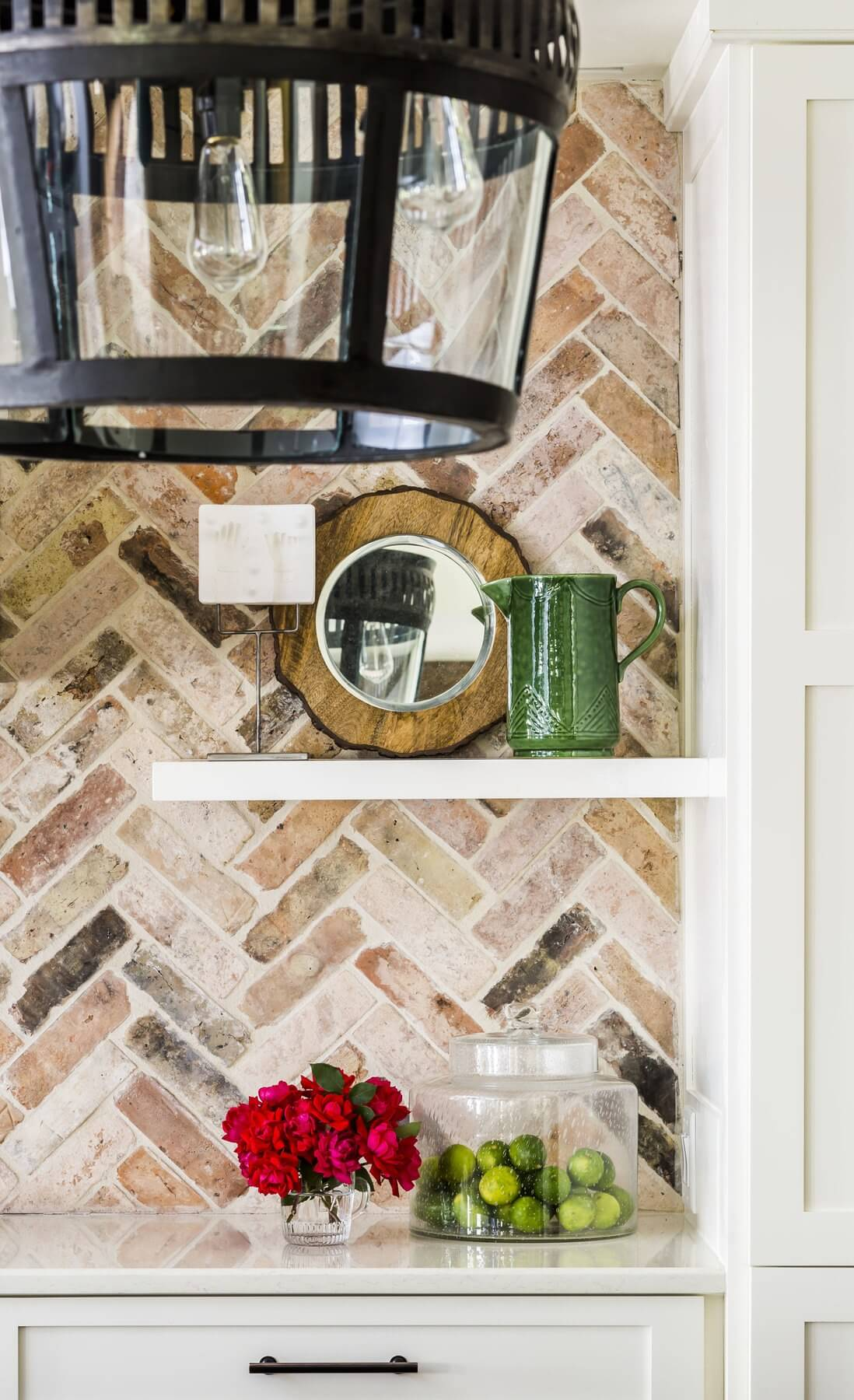 "Reclaimed brick lines the kitchen backsplash and other areas of the terrace level to add texture and instant ""age"" to the rooms."
