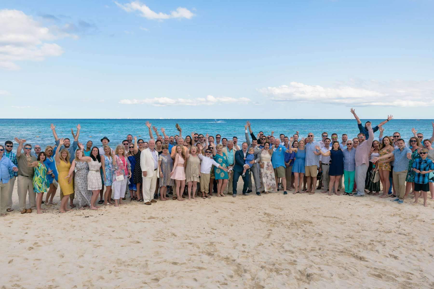 Friends gather on the beach to celebrate the new marriage after the ceremony.