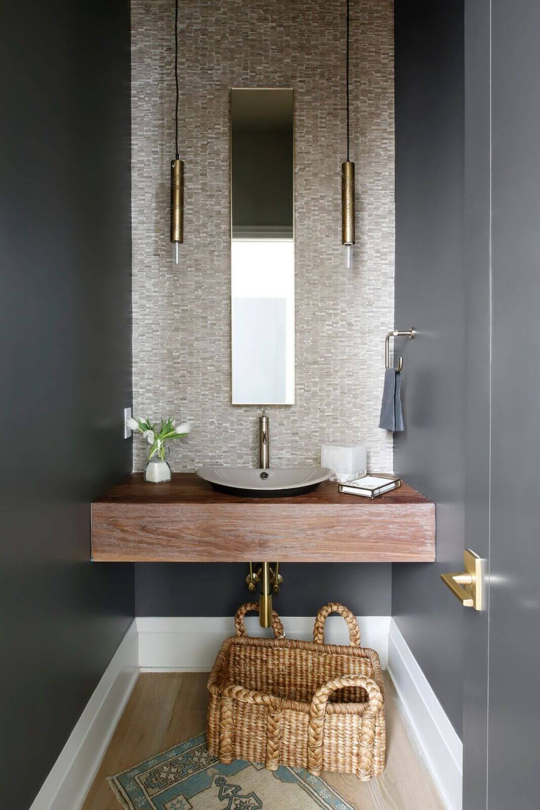 """This powder room is everyone's favorite,"" says Connie. ""We designed a custom wood shelf that houses a beautiful shallow ceramic bowl. The back wall is tiled in a very textured limestone mosaic. The mirror is intentionally small but functional, and the hanging brass light pendants have tiny sparkles of light. Walls are painted a dramatic dark taupe."""