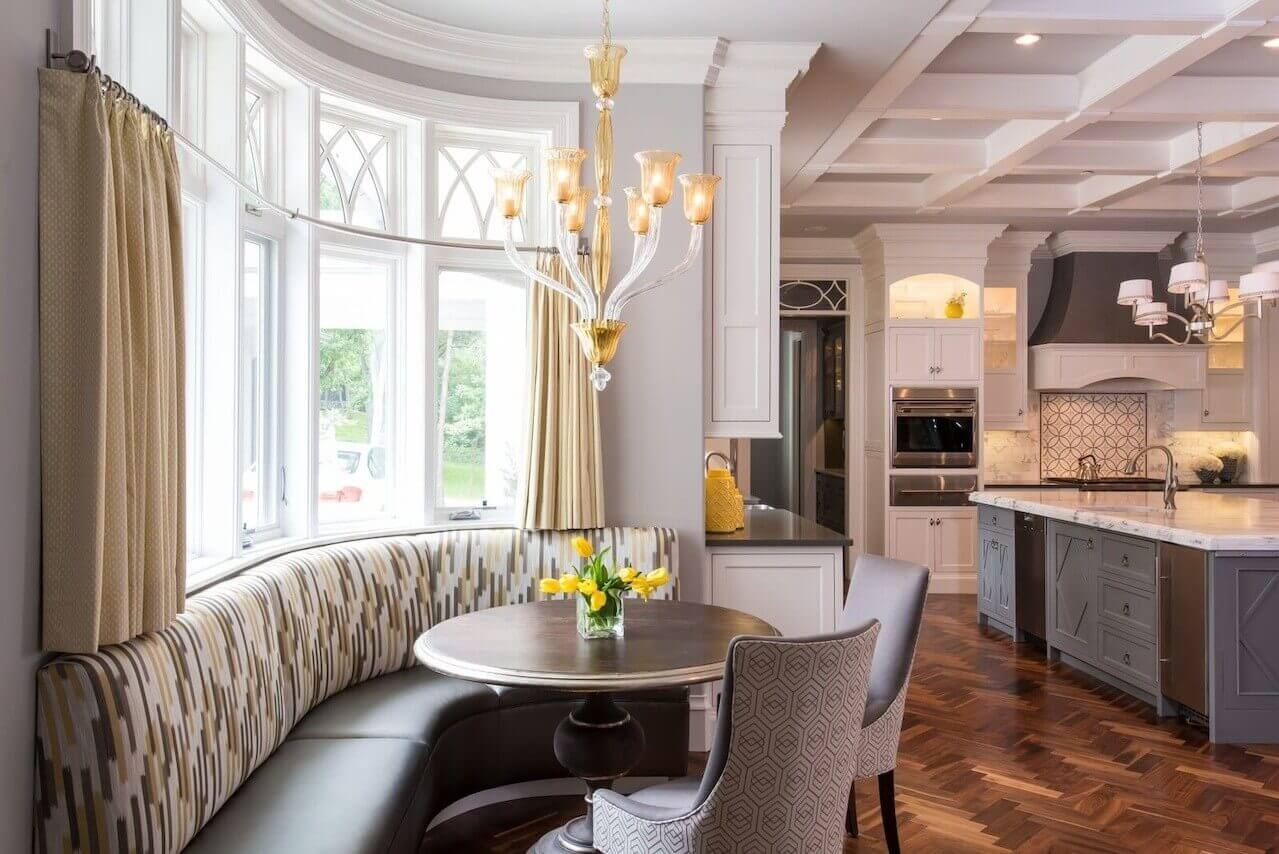 Gray and yellow tones distinguish the banquette area of the kitchen. Light fixture and table are by Arteriors, with patterned fabric is Robert Allen.