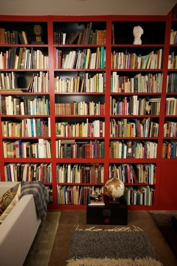 "Books are extremely important to the Erdreiches. ""The main feature of the foyer and little library is the massive wall of bookcases painted Chinese red with black interiors,"" says Jeremy. ""These, along with other details in the house, are chosen to better present the family's furniture, art and books."""
