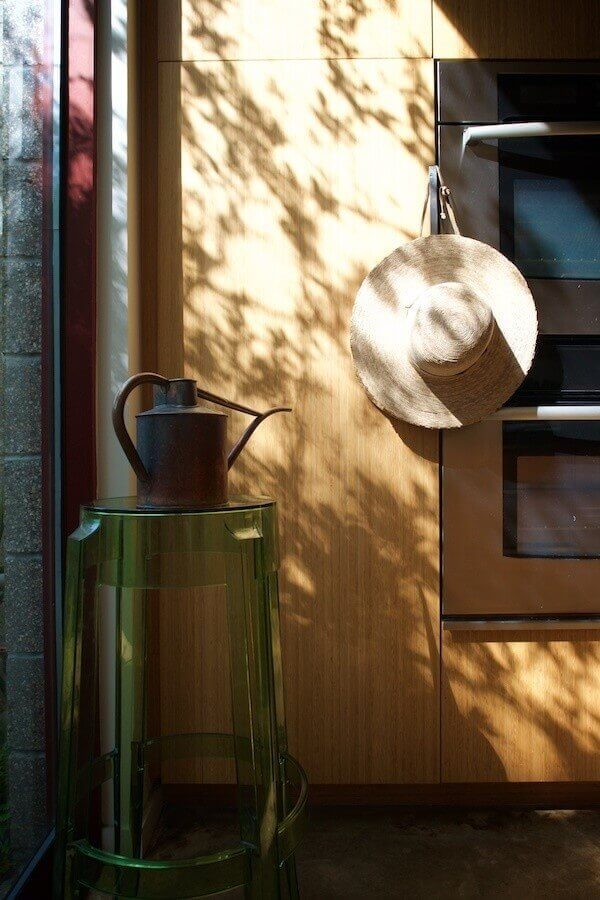 Ellen's gardening hat and watering can stand ready at the kitchen's entryway into the backyard garden.