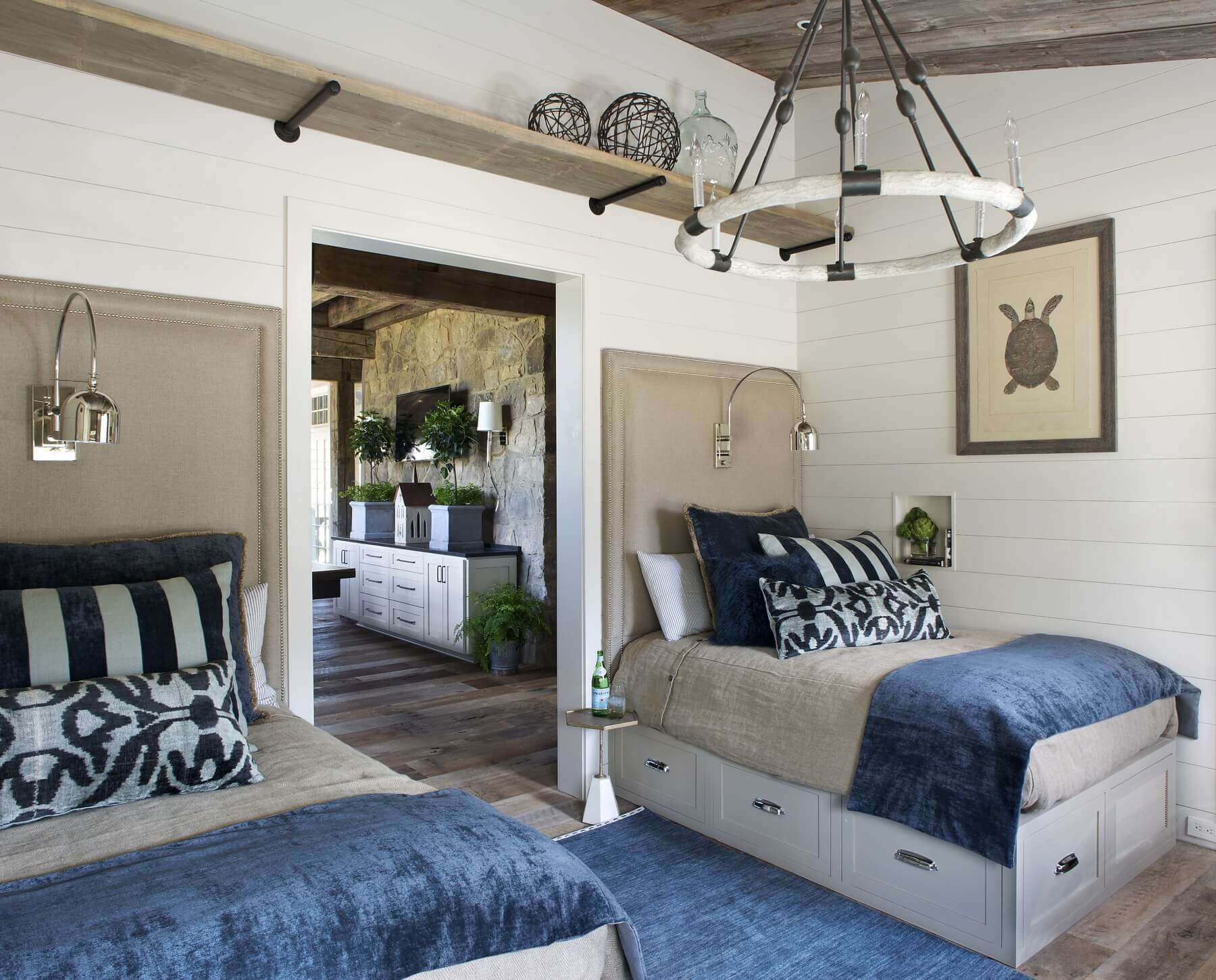 A bedroom features a pair of built-in beds with storage underneath, maximizing space and functionality for guests. A wagon wheel chandelier gives a nod to the home's rustic site.