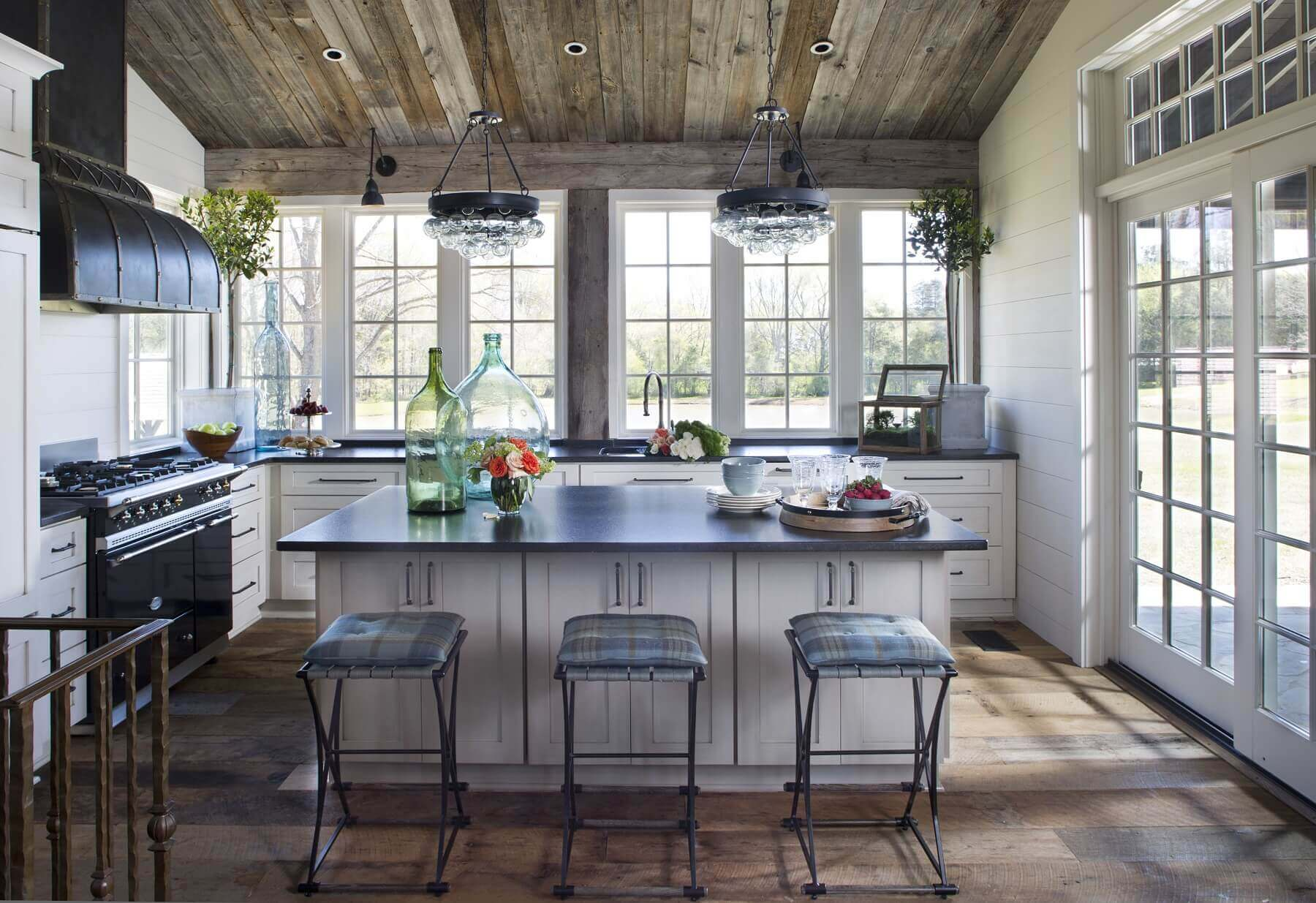 The kitchen is a light-filled space thanks to wide sliding doors and a line of large windows that replace upper cabinetry. The French Lacanche range is topped by a custom-made hood created by David Doss. A pair of glass orb light fixtures echo the larger, similar pendant fixture in the main entry.