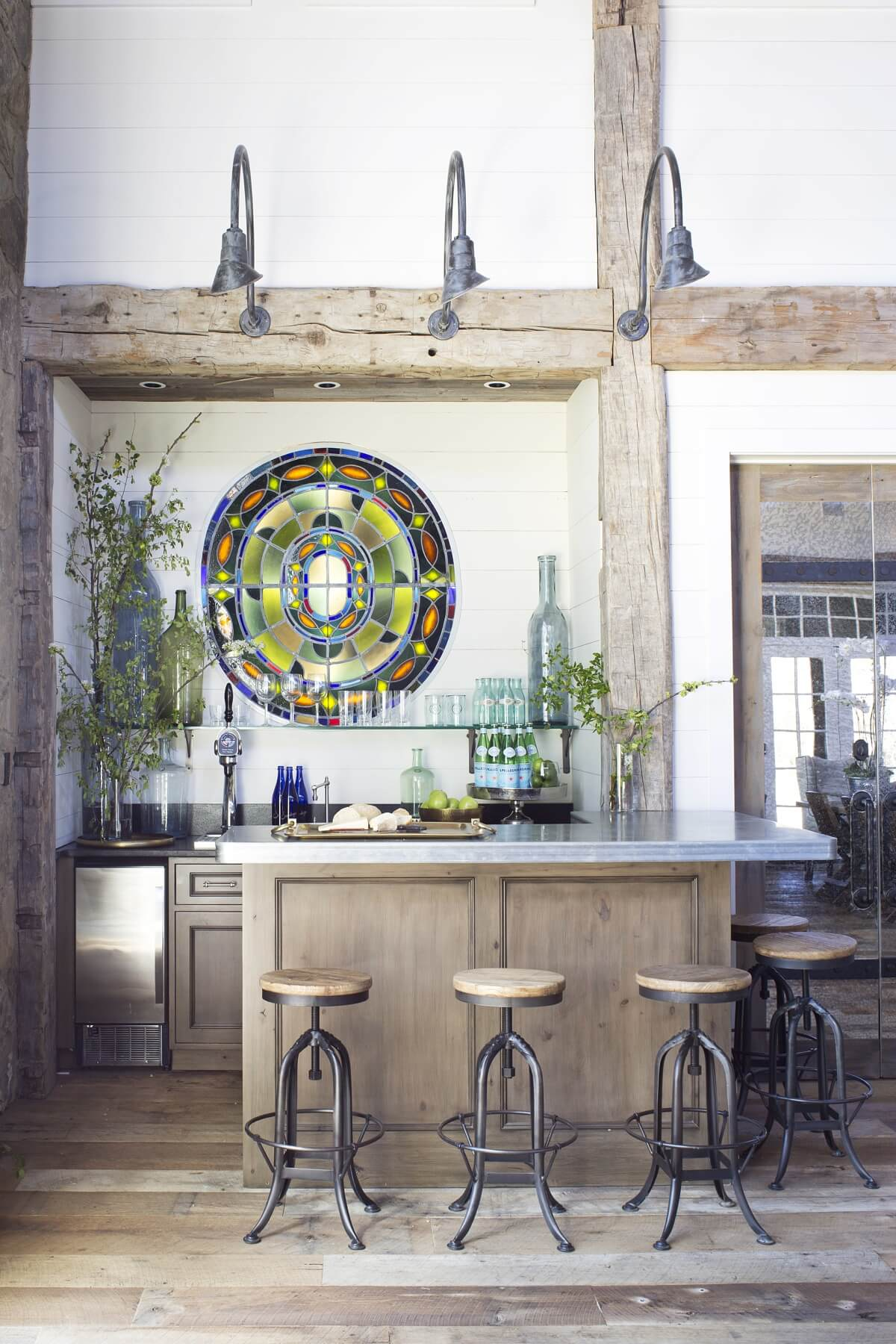 Behind the built-in wet bar, the design team installed a stained glass window that hails from the chapel of a historic Memphis building. It's embedded in the wall and backlit for maximum effect.