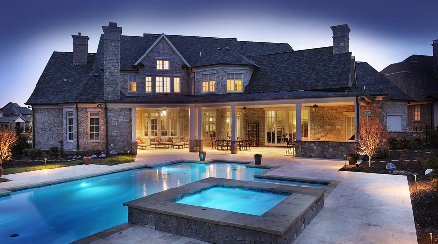 """LED lighting in the pool creates a fun, family atmosphere in the backyard and transitions the space from daytime to nighttime. The broad covered porch offers plenty of room for grilling and for family get-togethers, backyard barbecues, birthday parties and more. """"The whole softball team can come over and enjoy the pool and the fun lighting,"""" Brandon says."""