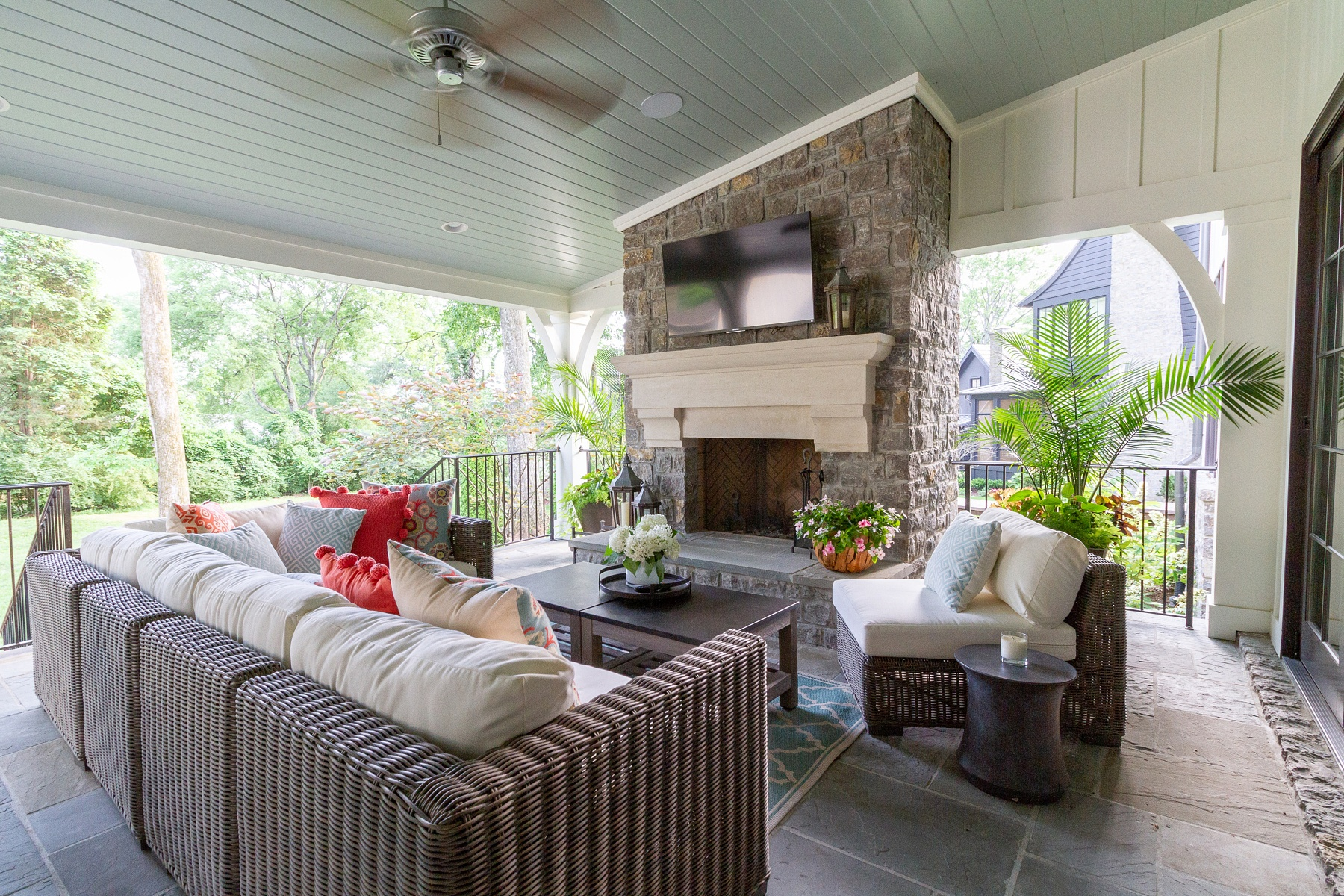 At the opposite end, this dreamy porch features a big, cozy stone fireplace that makes the outdoor living room even more inviting. The TV turns it into a perfect spot for watching fall football, too.