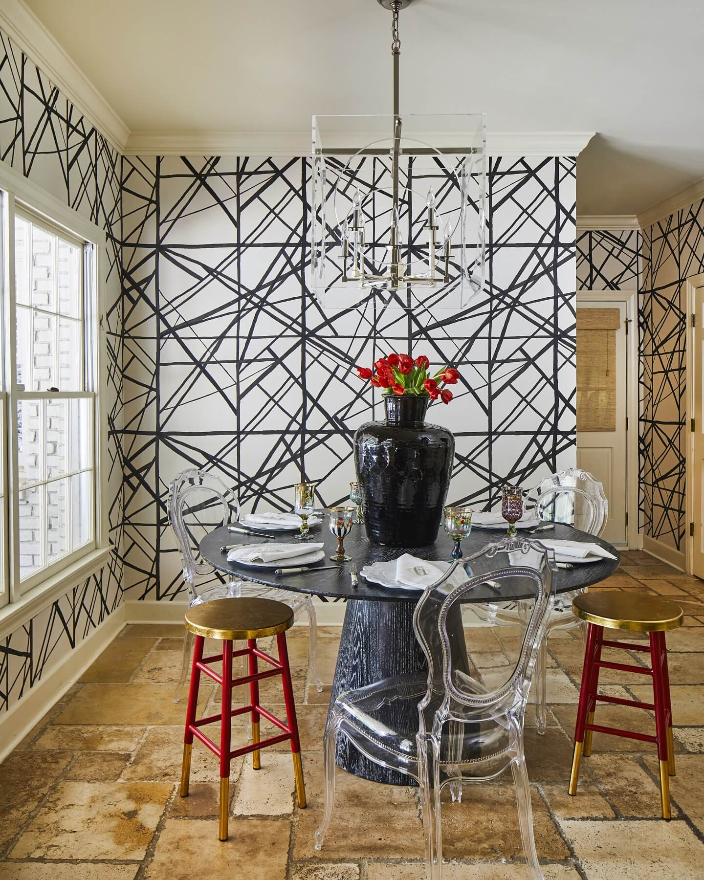 With its red gilded stools, acrylic ghost chairs, ghost chandelier, statement-making wallpaper and imposing modern table and centerpiece, this black-and-white dining nook is teeming with art-forward personality.