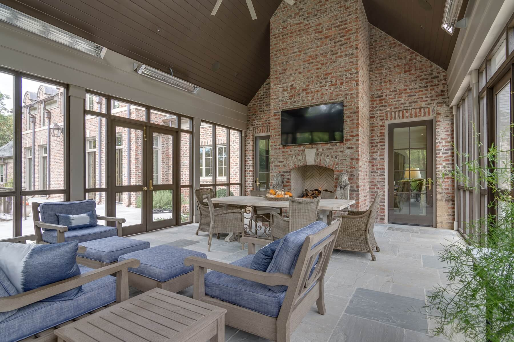 This spacious screened porch features a fireplace installed by bishop hearth home that adds warmth