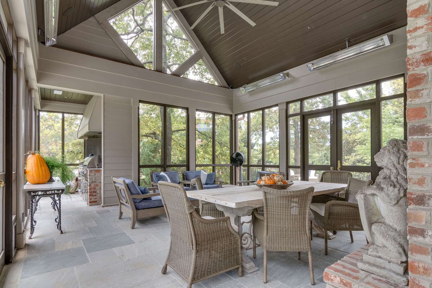 A wing of this roomy screened patio is the perfect spot for an outdoor kitchen. The outdoor vent hood lifts smoke away from the space, allowing the owners and guests to enjoy the porch while food is being prepared.