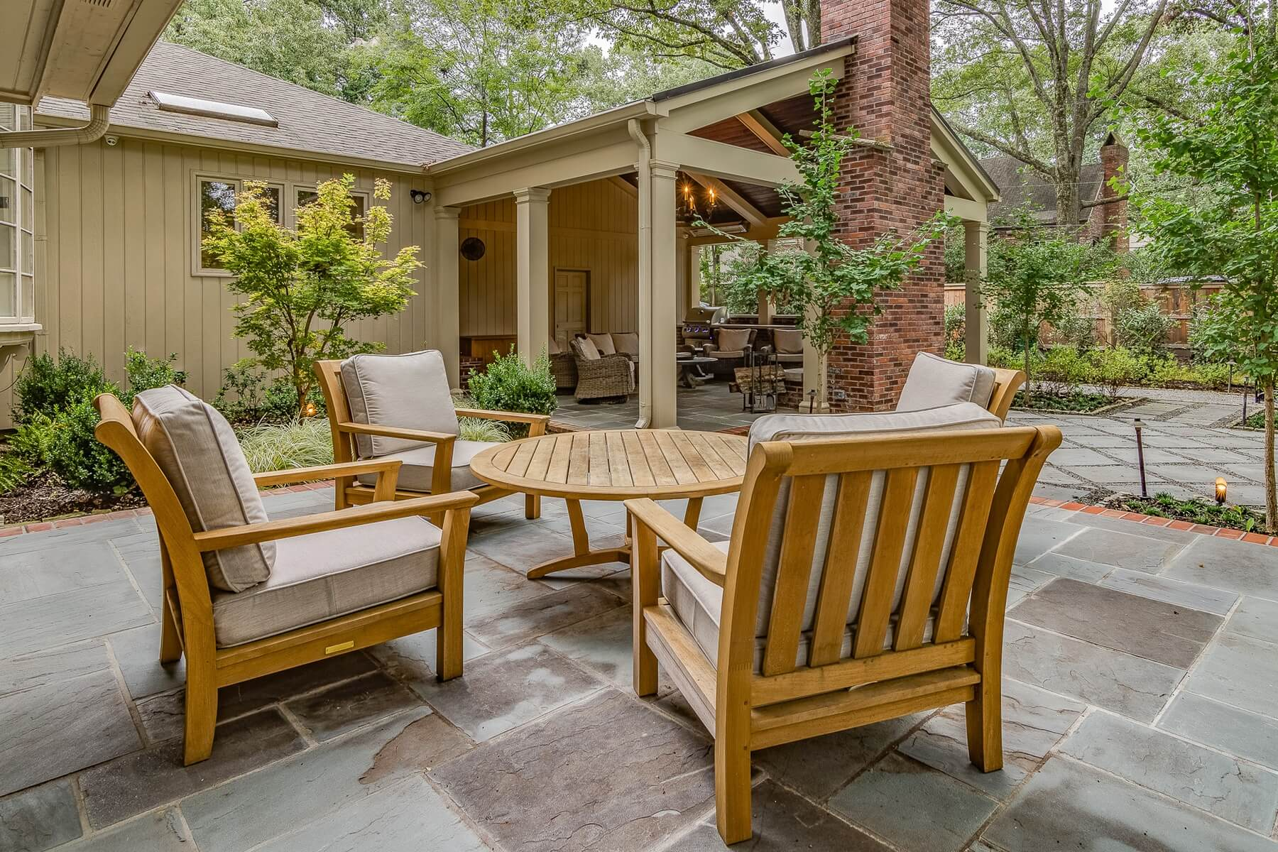 Bishop sells teak furnishings in a variety of styles to suit a variety of outdoor rooms. Teak stands up well in uncovered spaces, like this slate patio.