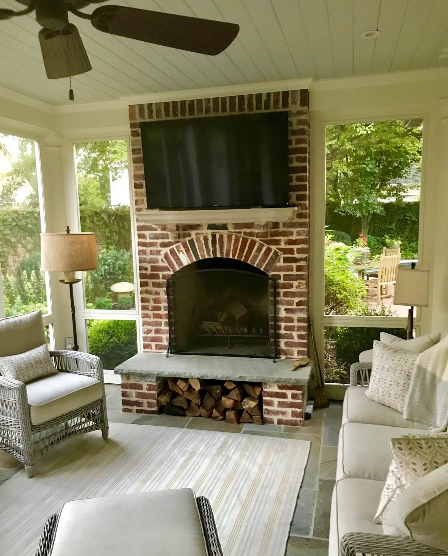 "On this screened porch, the fireplace area is designed for maximum comfort. ""We did the fireplace, and the brick mason did that log niche for them,"" says William. ""It's great to have — easy, close access to the wood, and it keeps it dry."""