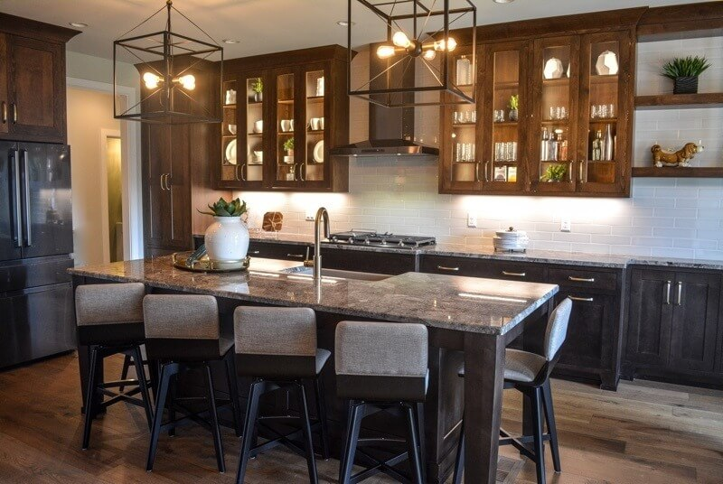 The open kitchen with granite countertops and built-in wooden cabinetry offers plenty of space for cooking, entertaining and family time.