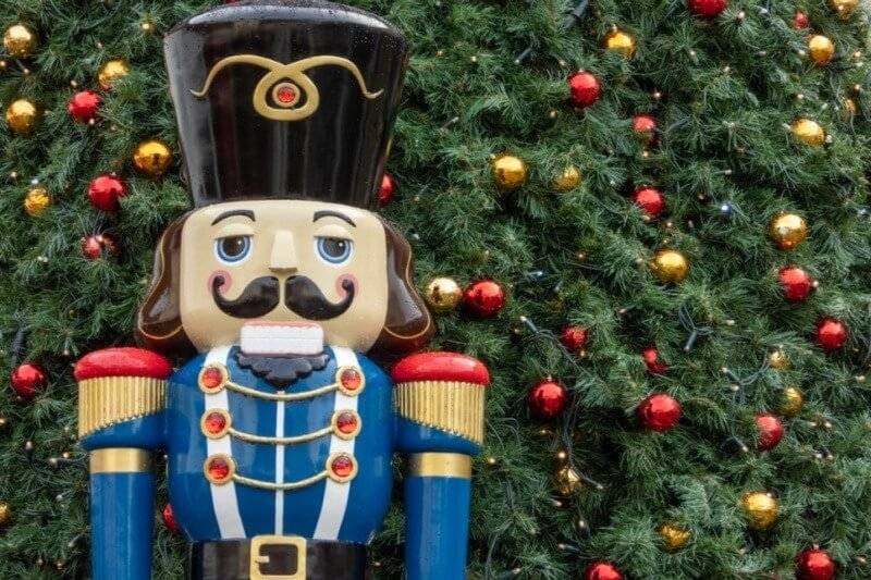 life-size nutcracker in front of Christmas tree
