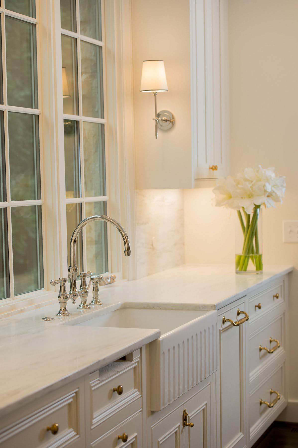 A Farmhouse sink, prep area and white cabinetry