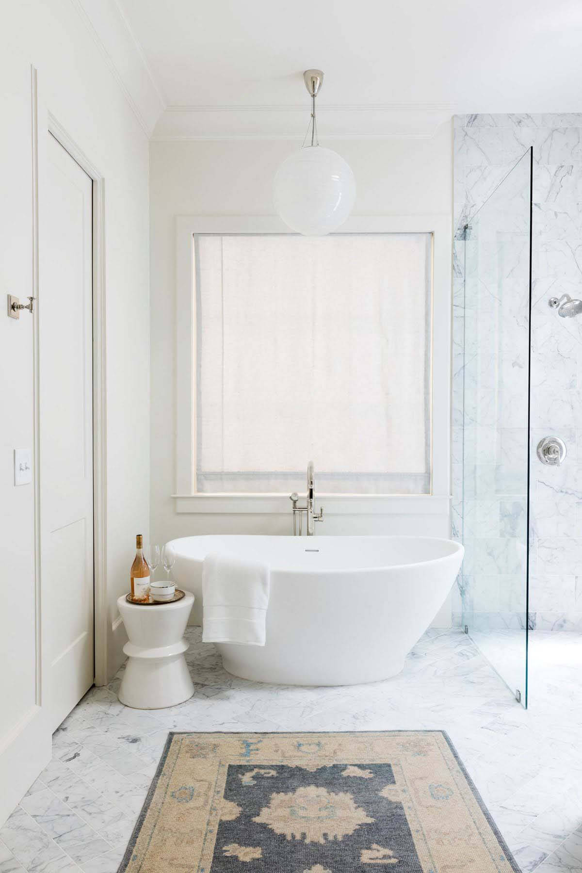 All-white master bathroom with vintage rug in Orr home
