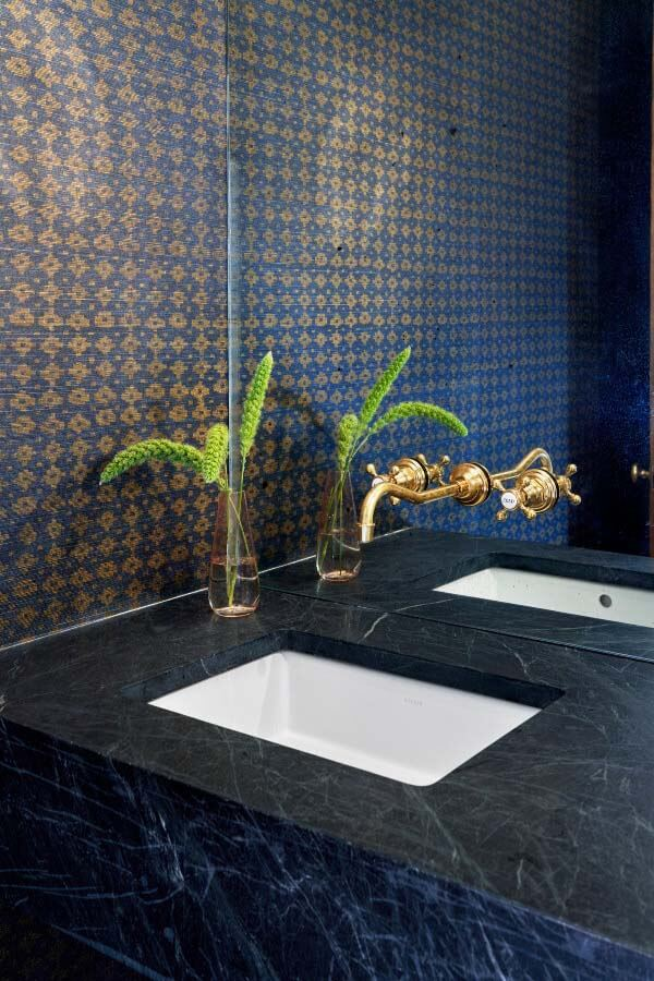 Powder room with navy and gold wallpaper, gold fixtures