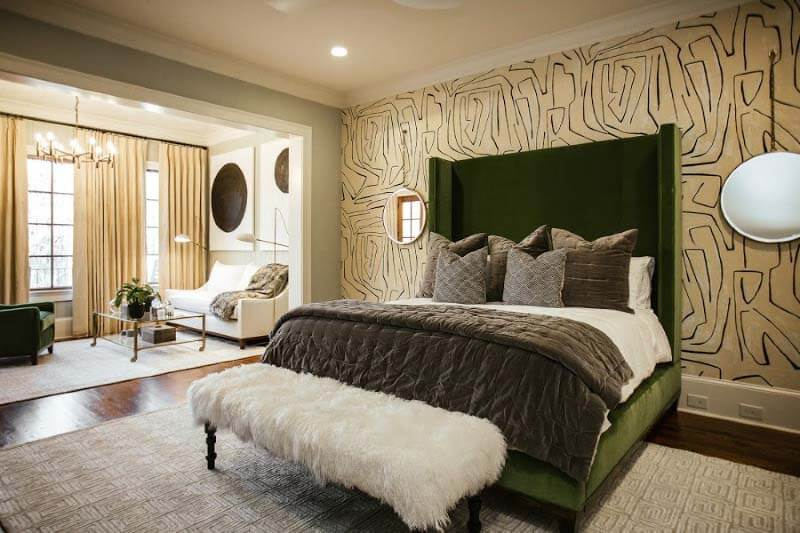 Master bedroom with fun wallpaper and green velvet bed