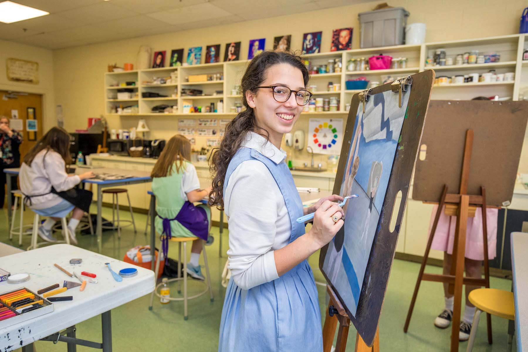 Young girls painting in art class