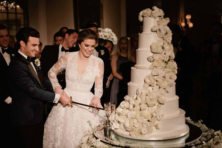 Cutting the cake with the family sword at a winter wonderland wedding | Photographer: Kristyn Hogan