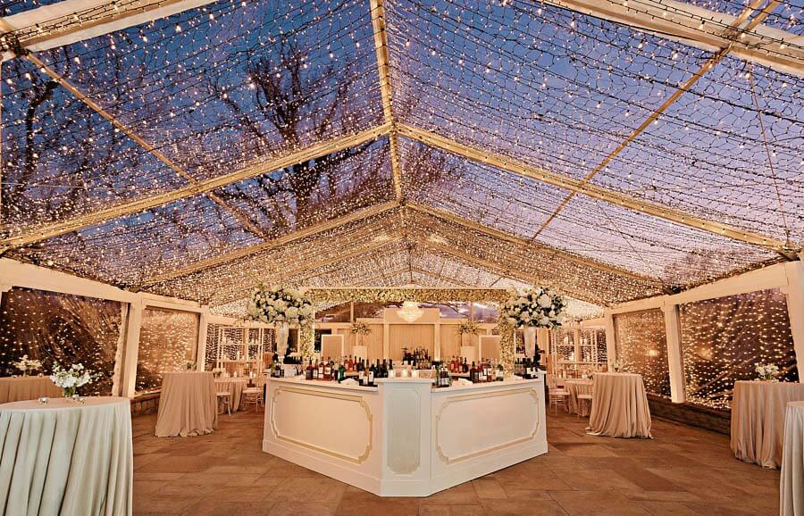 Tent and lights at sunset during a winter wonderland wedding | Photographer: Kristyn Hogan