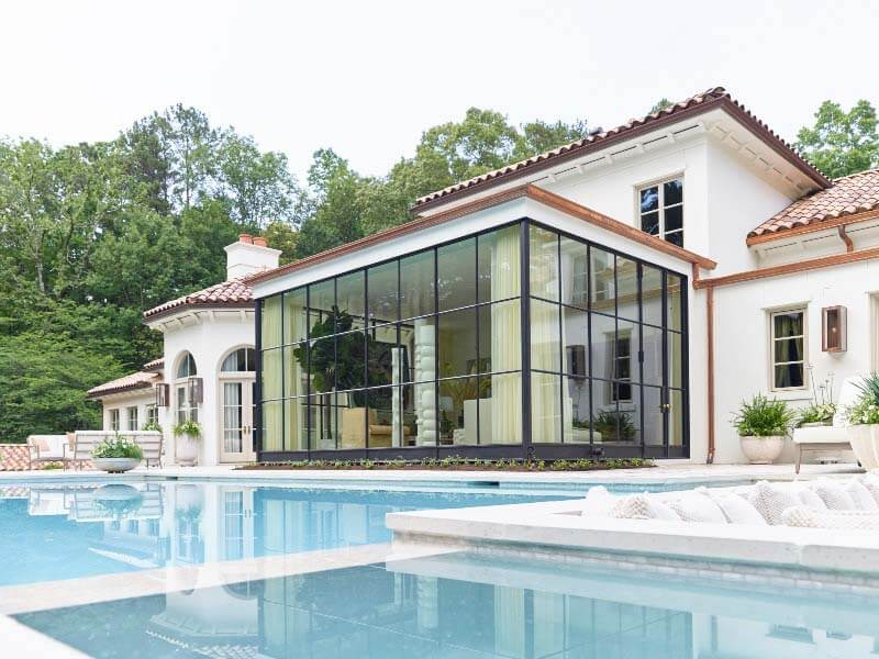 Close-up of pool and glass-encased room at back of house