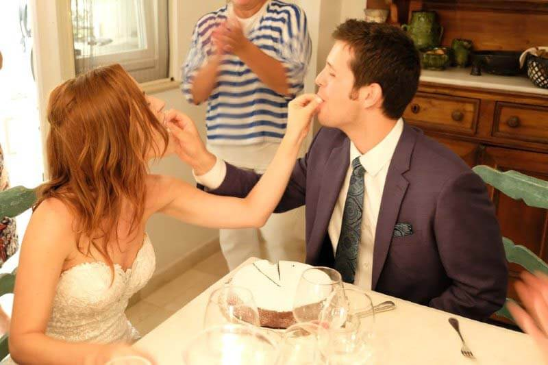 Aaron and Lacy feed each other a piece of the traditional Italian wedding cake.