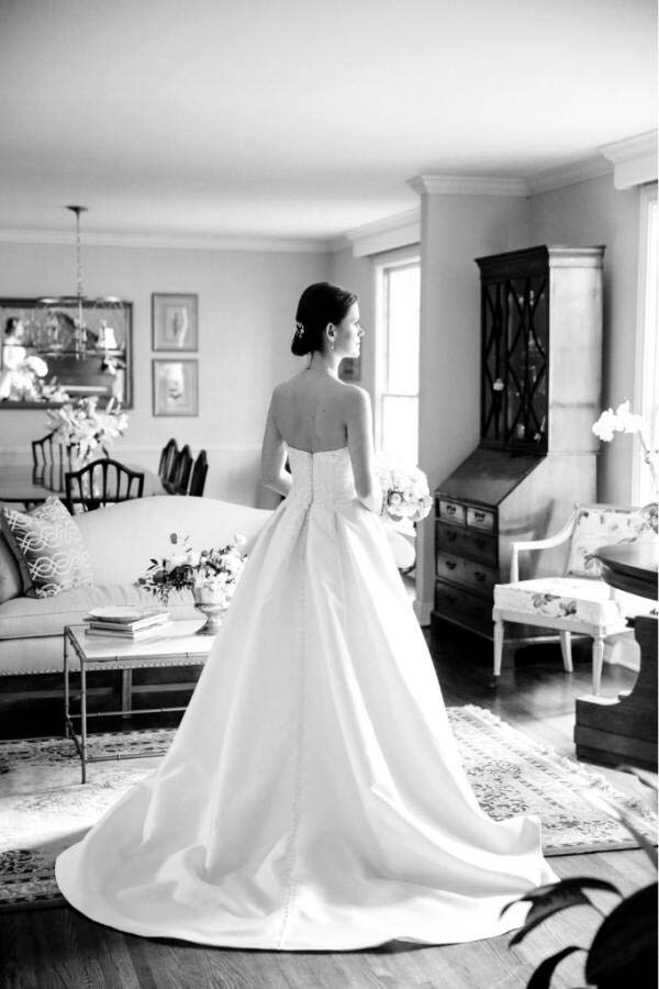 black and white photo of bride in her gown, with her back turned