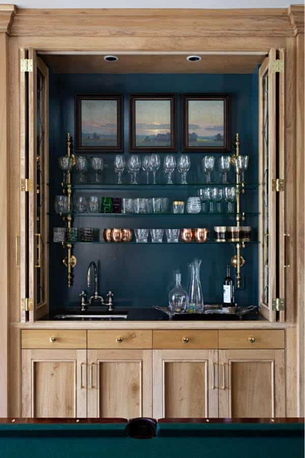 Open bar cabinet showing glassware and triptych