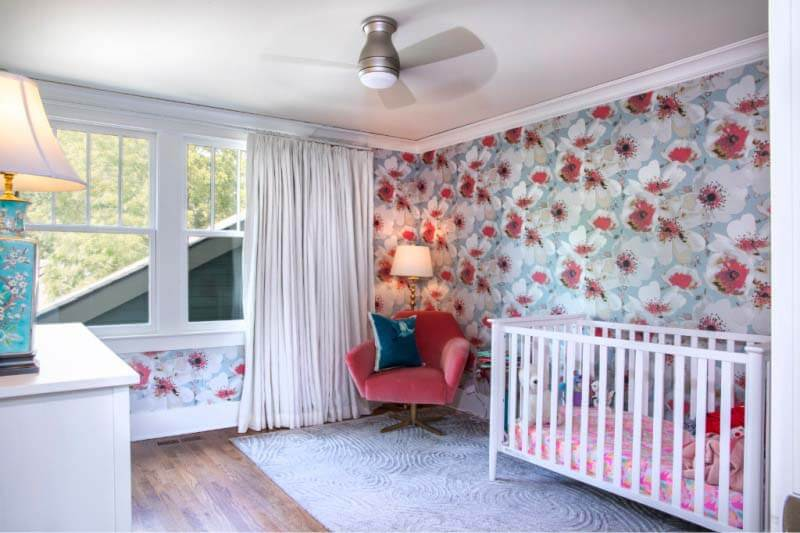 Girl's bedroom with crib and floral wallpaper