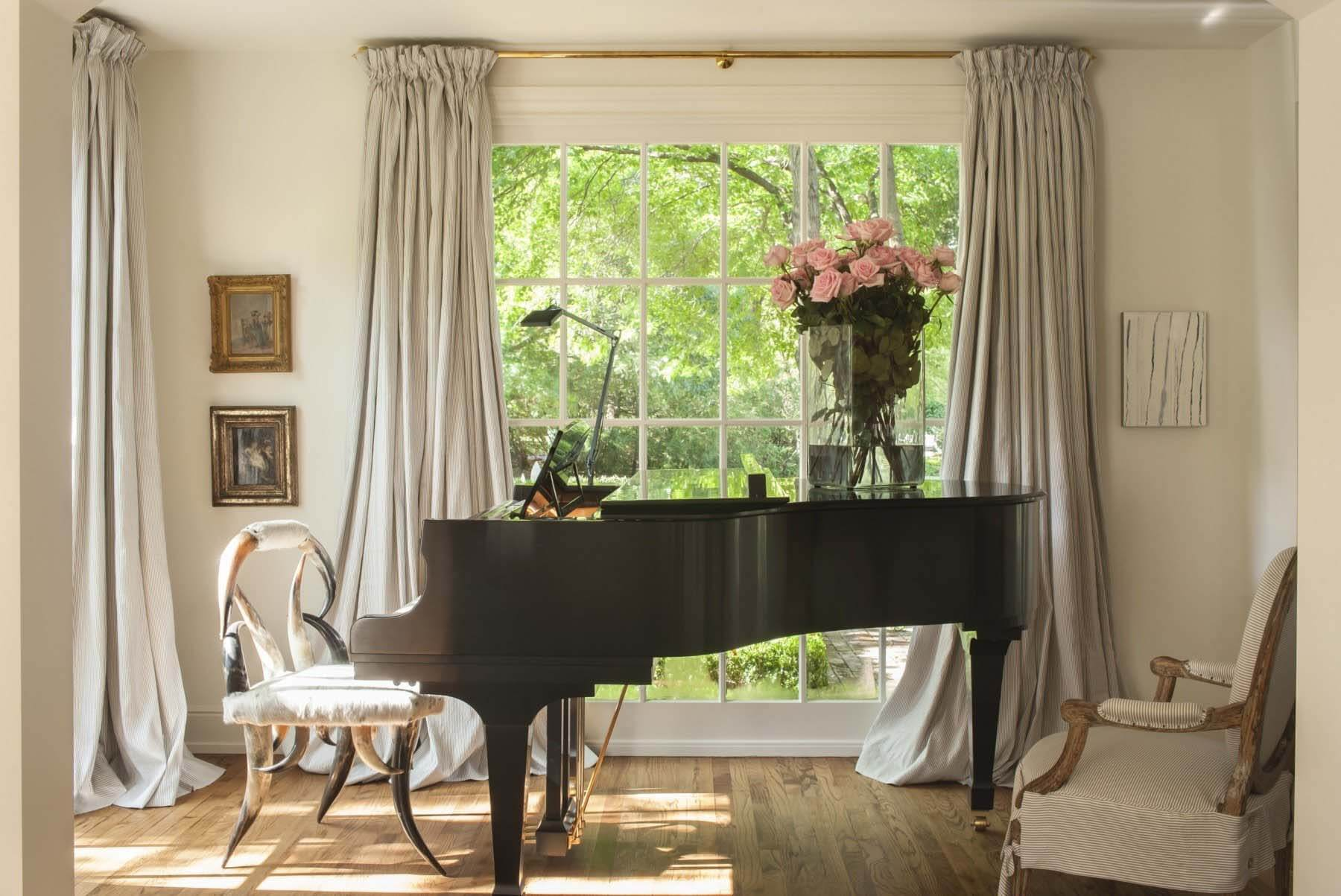 A piano room with unique chairs and ceiling-to-floor drapery