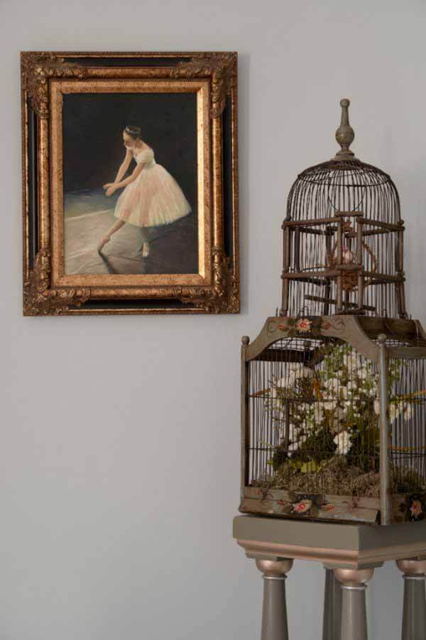 Birdcage with painting in the corner of the parlor at a renovated Victorian home