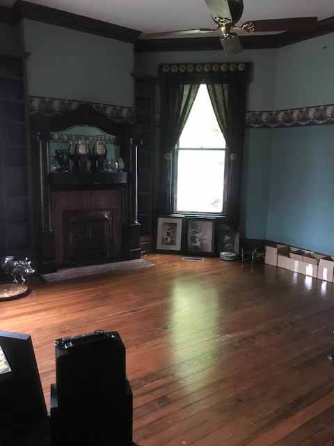 Pre-renovation photo of the library, with wood floor and dated blue wallpaper