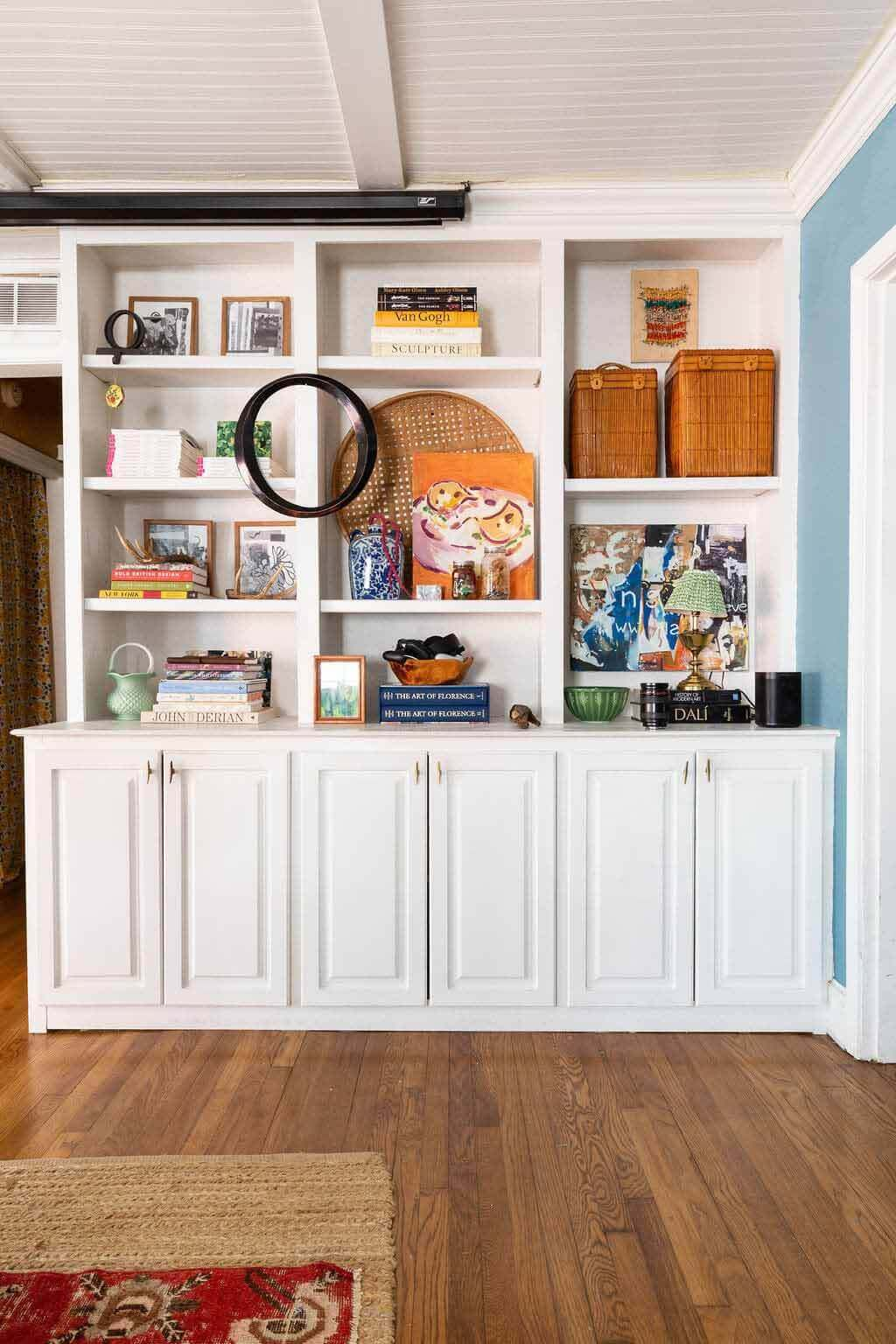 Art displayed in white built-in cabinets
