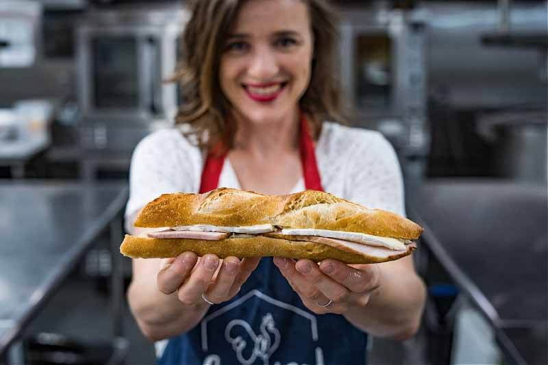 Elodie Habert of Cocorico holding a baguette sandwich made in Citizen Incubator Kitchens