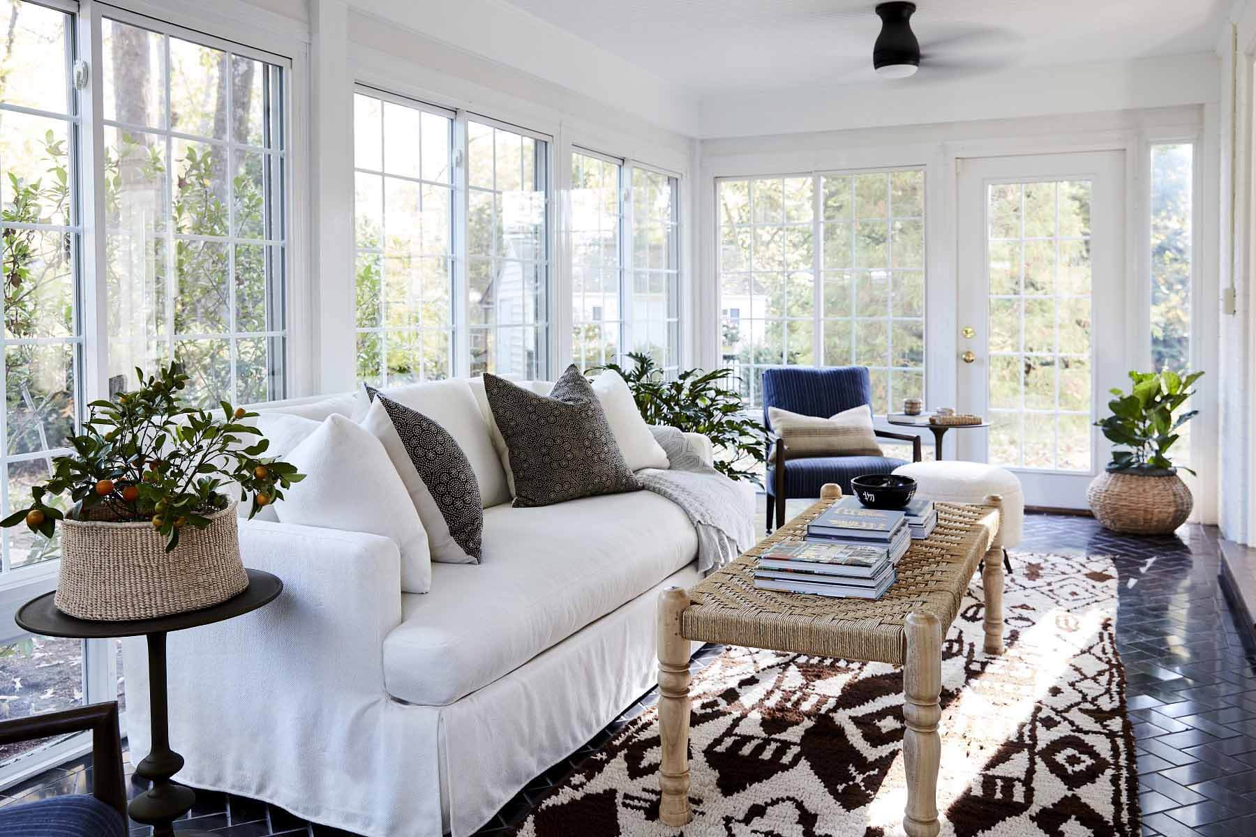 Floor-to-ceiling windows in a sunroom with a Moroccan rug and a white couch