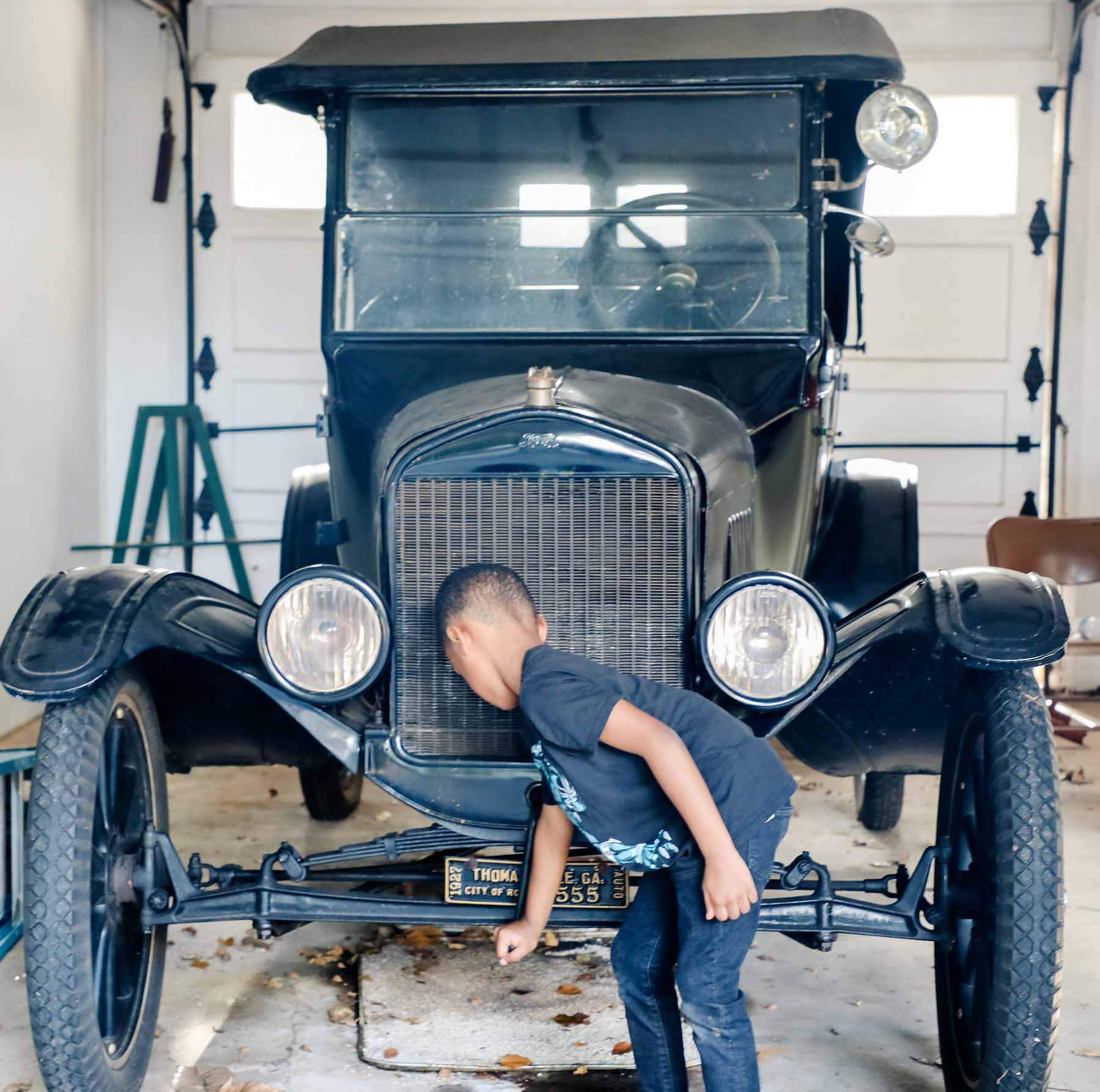 Young boy next to an old car at the Thomasville History Center