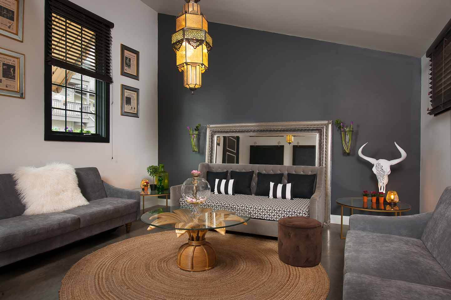 Living room designed by Esther Dormer with dark focal wall, three couches and antlers on the wall