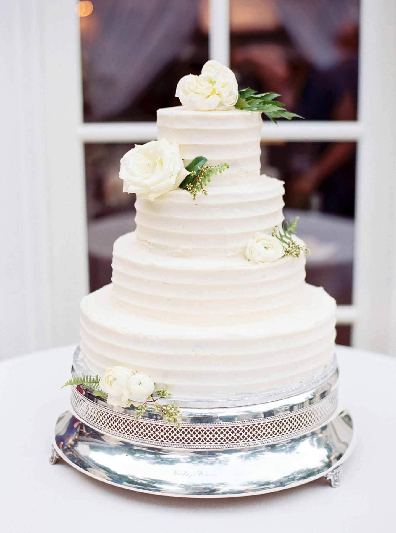 Four-tiered white wedding cake with fresh roses