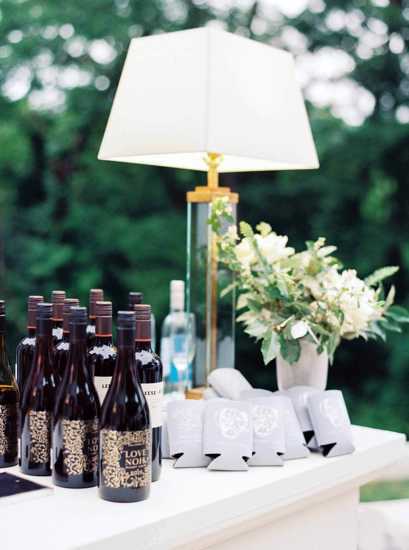 Bar setup with bottles of wine, flowers, lamp and koozies