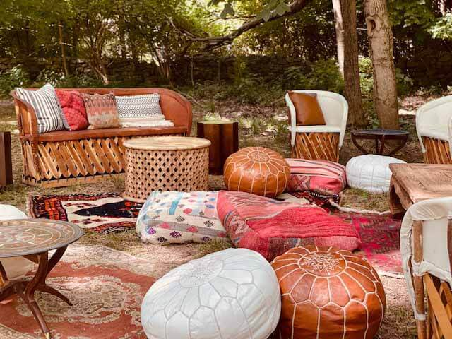 Outdoor lounge area with leather ottomans, rugs and couches