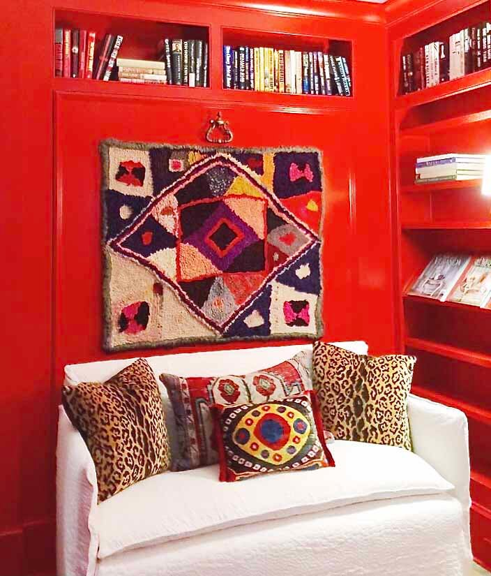 Bright red wall with geometric tapestry, behind a white loveseat with tapestry-covered pillows