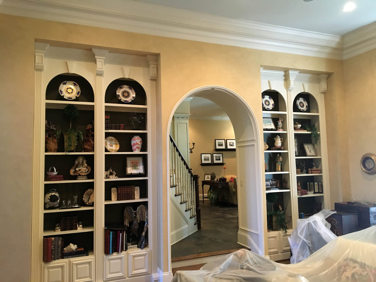 '90s home with outdated bookshelves and arched doorway