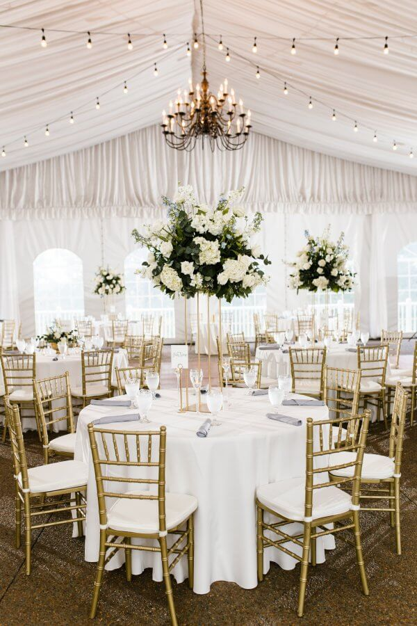 Wedding tent decorated with chandelier, round tables, gold chairs and white florals.