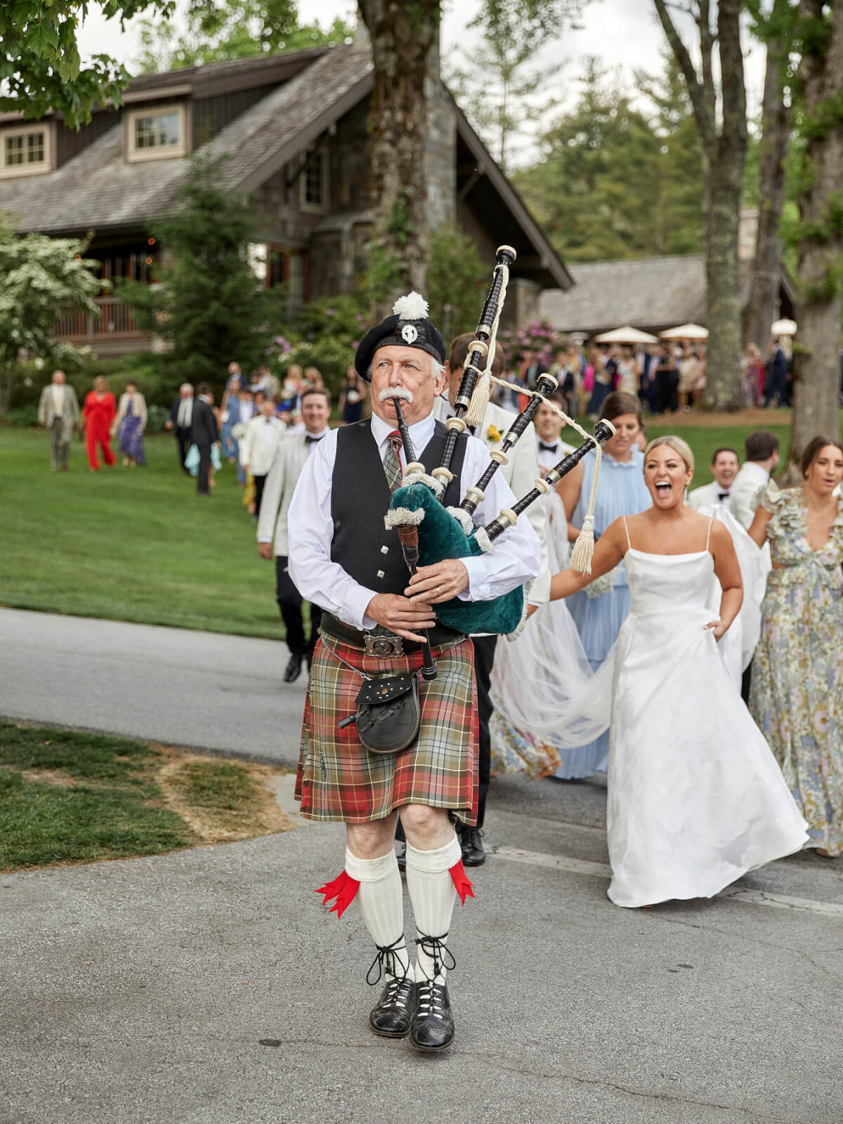 A bagpiper leads the bride, groom and their guests to the reception